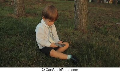 A little boy in black breeches, a white shirt with a tie, sitting on the grass and playing with a smartphone in the park. Sunset in summer.