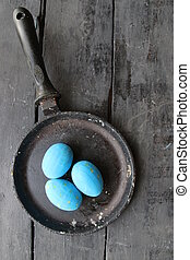 Easter eggs in a frying pan on rustic wooden background -...