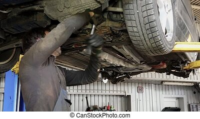 Male car mechanic with spanner working under automobile in...