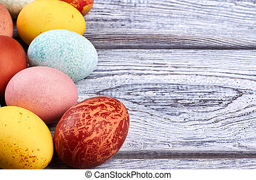 Colored eggs on wood. Easter eggs close up.