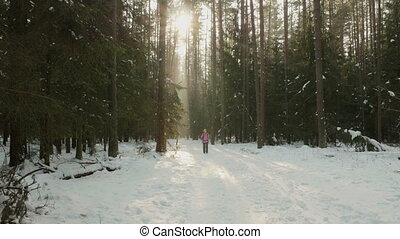 Young girl walks in the winter wood