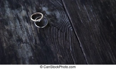 the rings of the bride and groom on wooden background