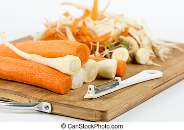 Peeled carrots and parsnips on the cutting wooden board