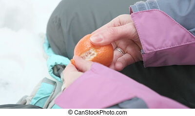 Young girl peels mandarin in the winter forest.