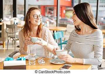 Two girlfriends having conversation at cafeteria