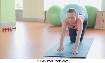 Girl doing warming up exercise for spine, backbend, arching stretching her back working out at home or yoga class.