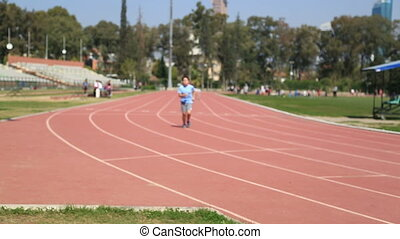 Child running on the stadium - Male teenage runner athletes...