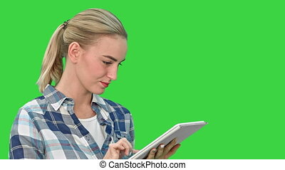 Portrait of a young woman using a tablet on a Green Screen, Chroma Key.