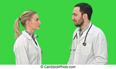Profile view of happy mature male and female doctors smiling while shaking hands on a Green Screen, Chroma Key.