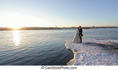 At sunset, the bride and groom stand on the river bank,...