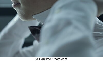 A young man in a black butterfly adjusts the collar of a...