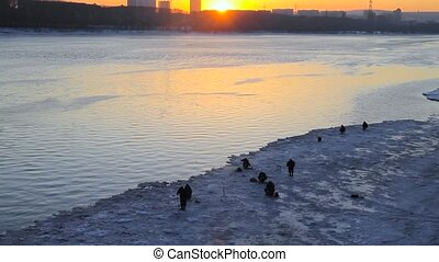 fishermen at sunset in winter - Winter fishing on the frozen...