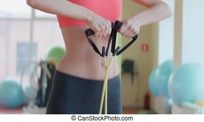 Nice girl posing with expander in fitness room.