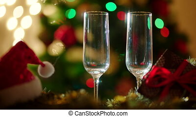 Two glasses filling with champagne on Christmas Eve. Santa...