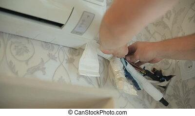 Repair Air Conditioner - Man repairing air conditioner at...