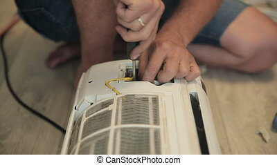 Worker Repair Air Conditioner - Man repairing air...