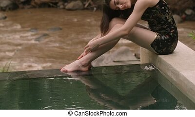 Young woman relaxing by the luxury pool - Sensual young...