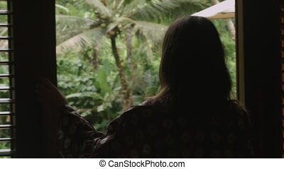 Woman walks out on terrace with view at jungle - Sensual...