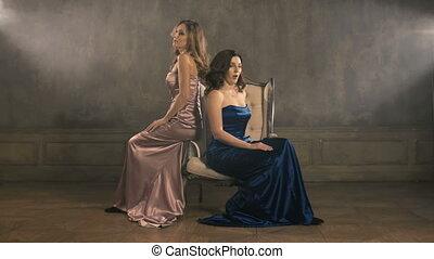 Two girls singer sit on a chair and sing. 4k longshot. Blue...