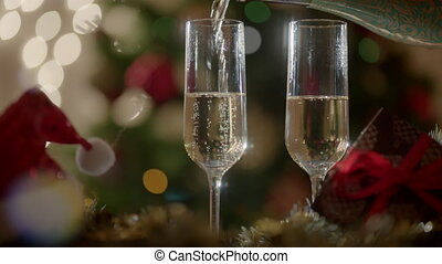 Filling two glasses with champagne on New Years party....