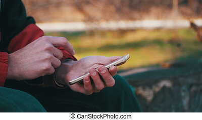 Young Man using a Mobile Phone on a Bench in the City Park....
