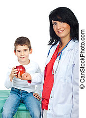 Smiling doctor giving apple to a child