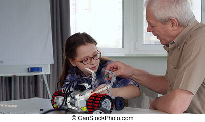Senior man gives his granddaughter the part from toy vehicle...