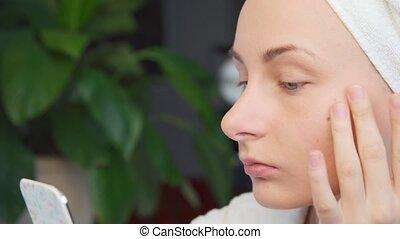 Beautiful young woman applying cream on face. - Beautiful...