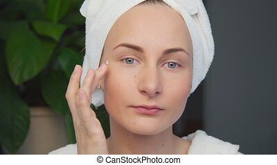 Young woman applying cream on her face.