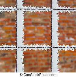 Rusty wire fence covered with frost and hoarfrost with blurred bricks background in the winter. Textures.