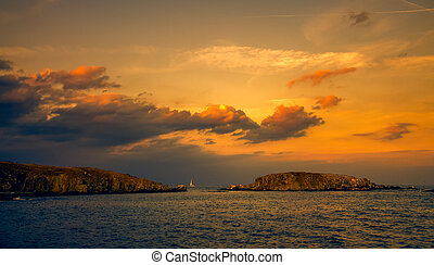 panoramic evening view of two islands at sunset
