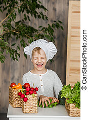 Handsome little kid in chef uniform with vegetables. Cooking in kitchen at home. Vegetarian. Healthy food