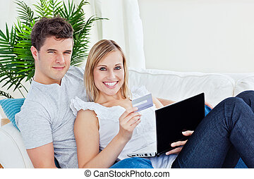 young couple with laptop and credit card bying online lying in the living-room