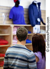 rear view of a young couple looking at men clothes standing...
