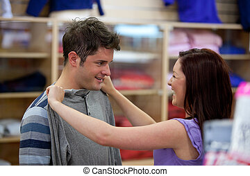 cheerful couple choosing clothes standing in the men...