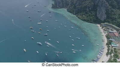 Aerial drone video top view of sailing boats in the bay of iconic tropical Phi Phi island