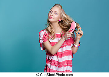 young attractive blond woman brushing her hair with pink...