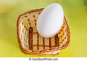Large white goose egg in a brown basket, close up, yellow...