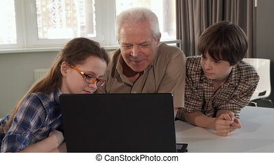 Children and their grandpa watching something on laptop