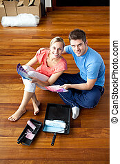 Beautiful couple sits on the floor picking colors