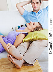 happy couple relaxing together lying on the sofa at home