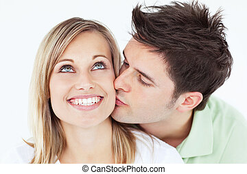 careful man kissing his smiling girlfriend against a white...