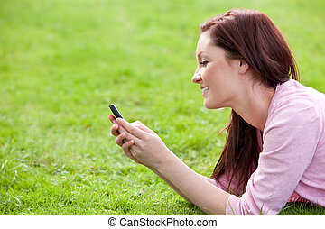 Attractive woman using cellphone lying on the grass