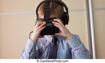 Little boy use virtual reality headset helmet, he very...