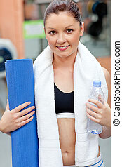 sporty woman holding bottle of water and exercise mat...
