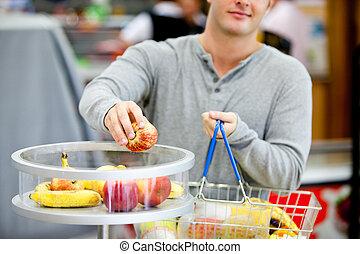 primer plano, el suyo, compras, joven, poniendo, manzanas, cesta, hombre