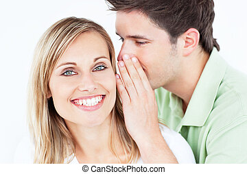 handsome man whispering something to his girlfriend against...