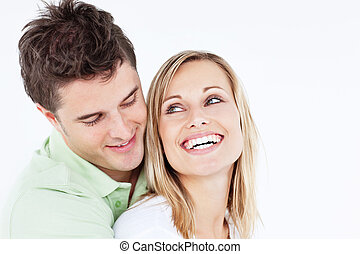 handsome man hugging his laughing girlfriend against a white...