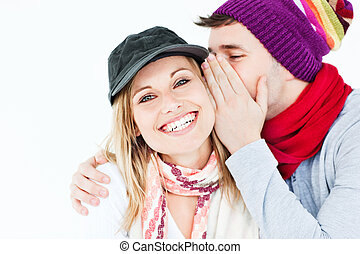 young man with cap whispering something to his female friend...