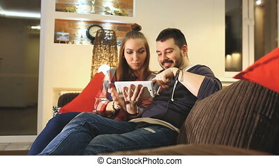 Couple using digital tablet touchscreen ipad watching...